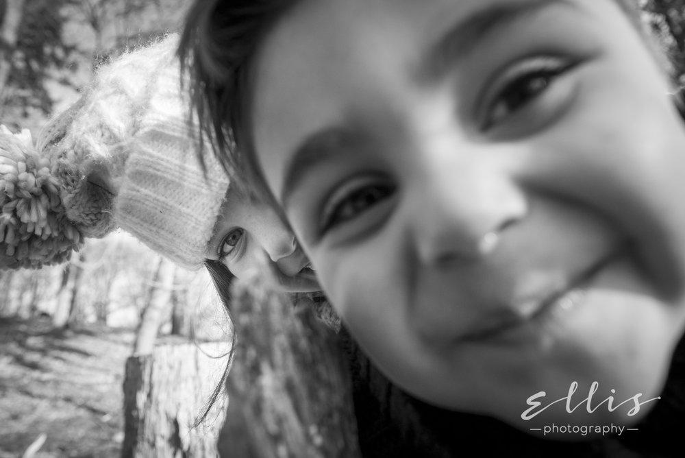 Close up van een jongetje en zijn zusje. Zwart wit portret fotografie door Ellis Peeters Photography.