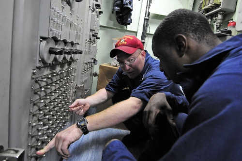 Interior Communications Electrician Zachariah Deaver trains Electrician's Mate Jermichael McDuffie aboard the USS Comstock (2011)