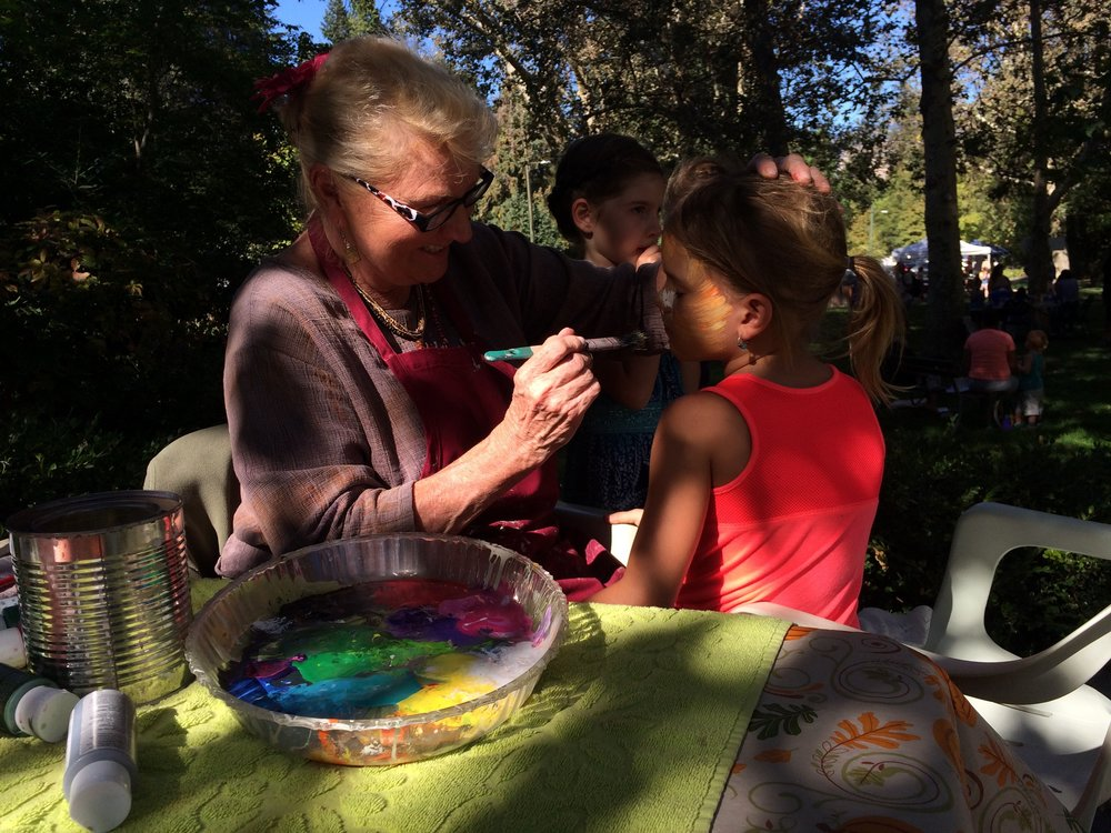 Face paint artist Pam Galusha transforms a festival goer into a summer fox.