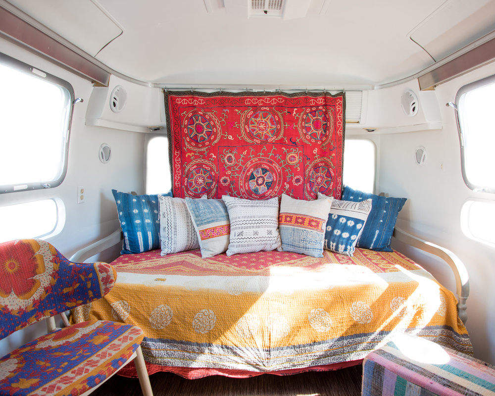 The interior zoomed out view of the vintage airstream. On the day bed we have a kantha blanket from India. As a curtain we have a vintage silk suzani from Uzbekistan, and on the bed are pillows made locally in Asheville made of mud cloth from Mali and batik indigo from northern Vietnam.