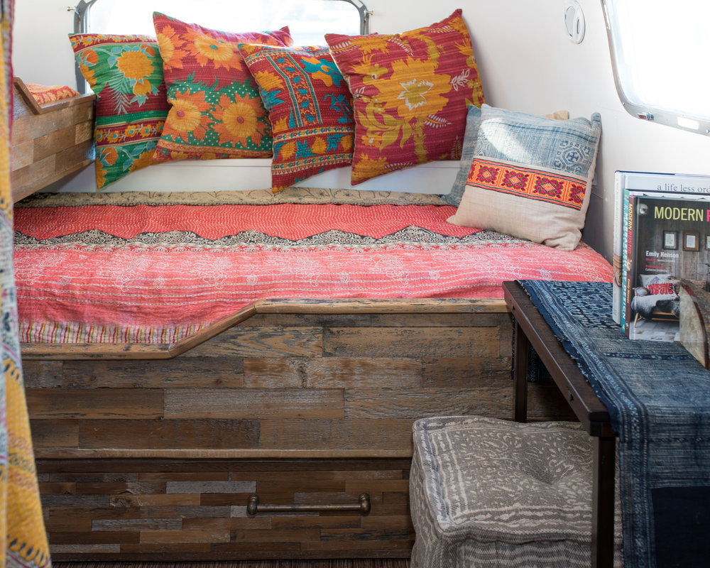 For the back of the airstream we wanted to make it colorful and inviting! We used vintage kantha blankets from india on the bed and then threw some gorgeous and vibrant pillows on there. One of the best parts about these beautiful pillows is that they are machine washable. On the table next to the bed we have a piece of fabric from northern vietnam and a pouf to sit on.