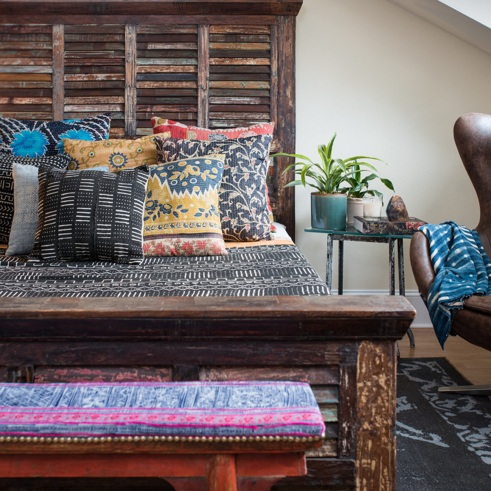 Assortment of vintage kantha pillows and mud cloth from western Africa on a painted teak bed.