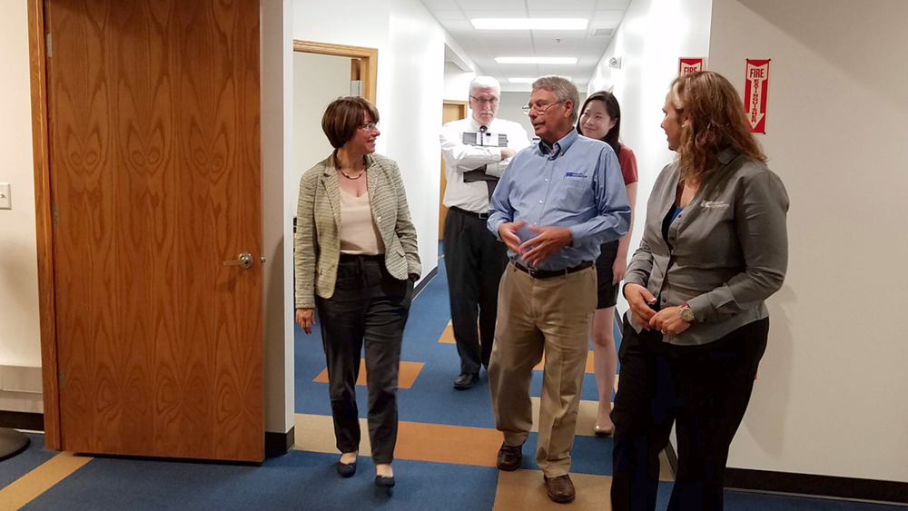 Wayne Kahler shares details of Kahler Automation's operation as Chantill Kahler Royer, Sen. Klobuchar, and her staff listen.