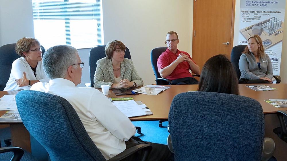 Sen. Klobuchar asks for details on Kahler Automation's history, as Fairmont Mayor Debbie Foster (left) and others listen on.