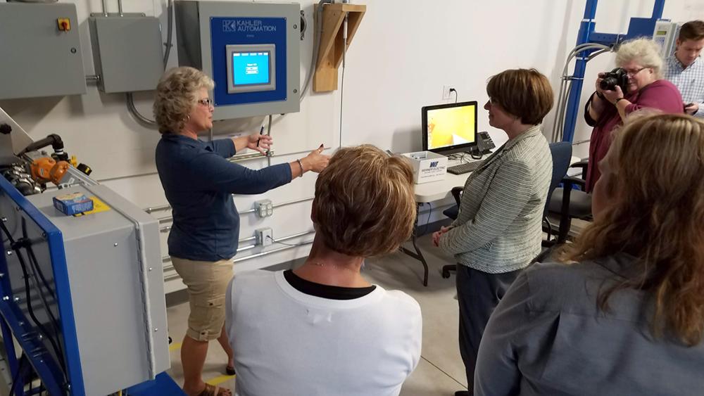 HMI Programmer Kristi Prafke begins to explain Kahler's laser-guided, automated tripper control to Sen. Klobuchar.