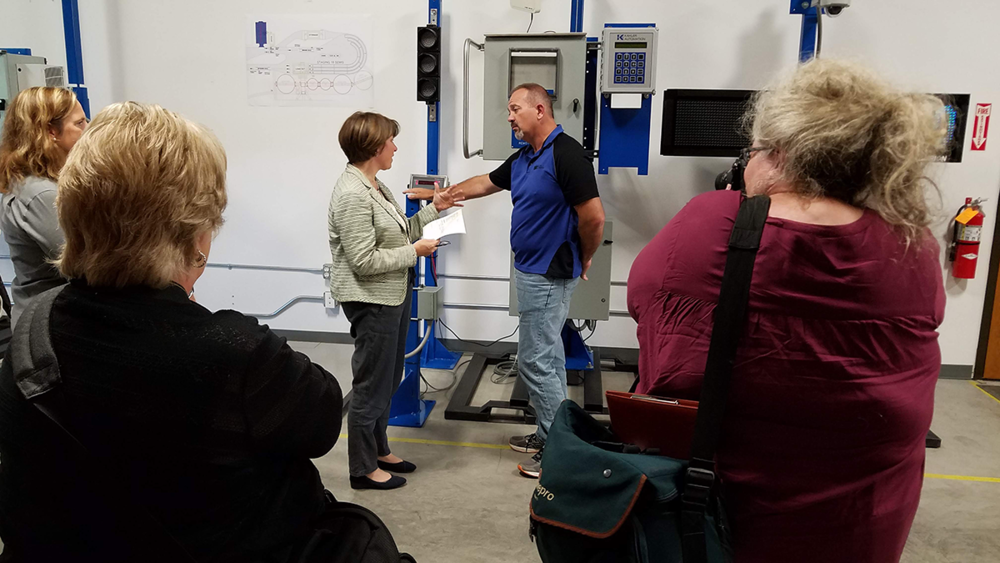 Sen. Klobuchar asks Paul Rehm for examples of applications for Kahler's truck traffic control system, as local media document the Senator's visit.
