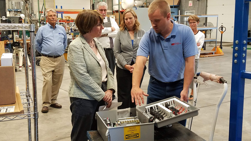 Wayne Kahler, Klobuchar southern Minnesota outreach director Chuck Ackman, Chantill Kahler Royer, and Mayor Foster look on as Jordan Honnette shows the Senator the inside of a control panel.