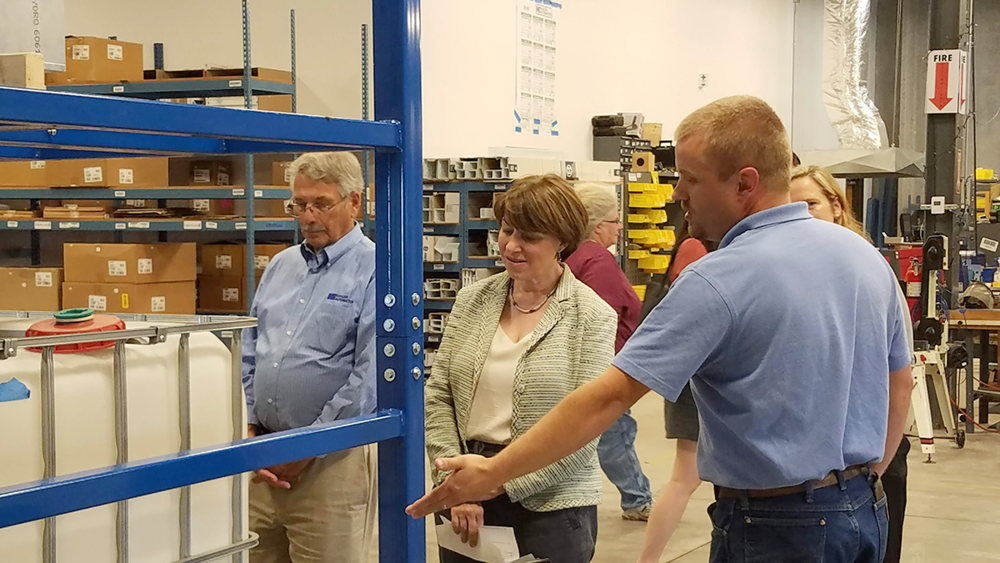 Jordan Honnette explains the workings of a Kahler Automation high-speed tote filler to Sen. Klobuchar.