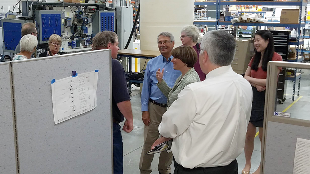 Lead Technical Support Specialist Phil Wakey (wearing headset) was one of many Kahler Automation employees that Sen. Klobuchar made a point to stop and chat with during the tour.