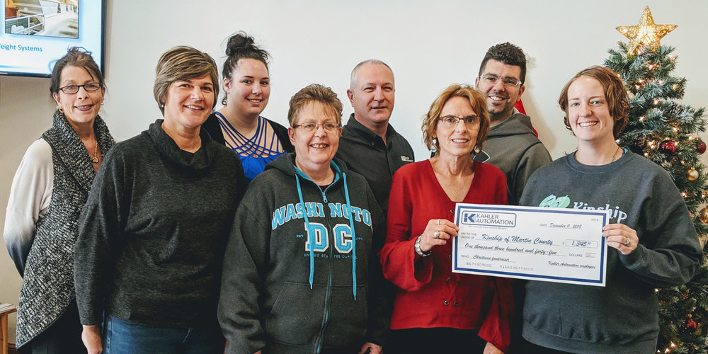 "KINSHIP OF MARTIN COUNTY ACCEPTS CHECK FROM KAHLER AUTOMATION'S ""BISON COMMITTEE"" MEMBERS — L-R: Martha Myren, Courtney Cutler, Megan Hancock, Darla Mammenga, Brian Enstad, Norma Seibert, Max Haake, and Kinship of Martin County associate director Jen Kahler."