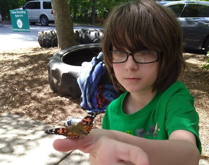 Author's son with a butterfly we raised at Pathfinder from a caterpillar.