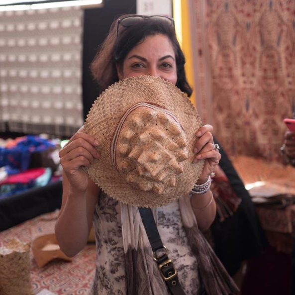 Anju holding one of Edric Ong's signature Iban hats. Ong creates a contemporary version of the traditional Iban's man's 'topi tunjang' rattan hat with an additional brim and a handwoven ikat hatband.