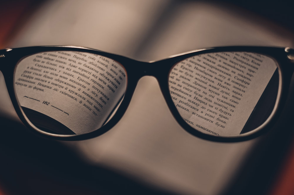 A photo through the lens of a pair of glasses, focusing on the pages of a book.