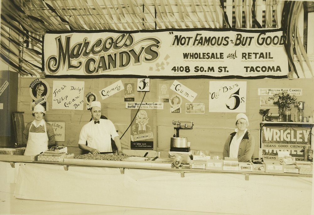 "Founders Dora Marcoe (Left) and Floyd Marcoe Sr. (Center) at the original Marcoe's Candy stand at the Washington State Fair circa 1930. The original company slogan was ""Not Famous - But Good"""