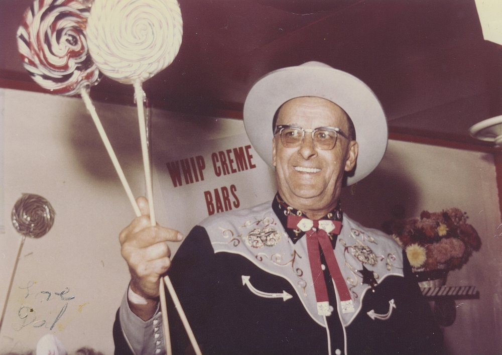 Floyd Sr. holding two jumbo whirly pops in his favorite cowboy outfit.