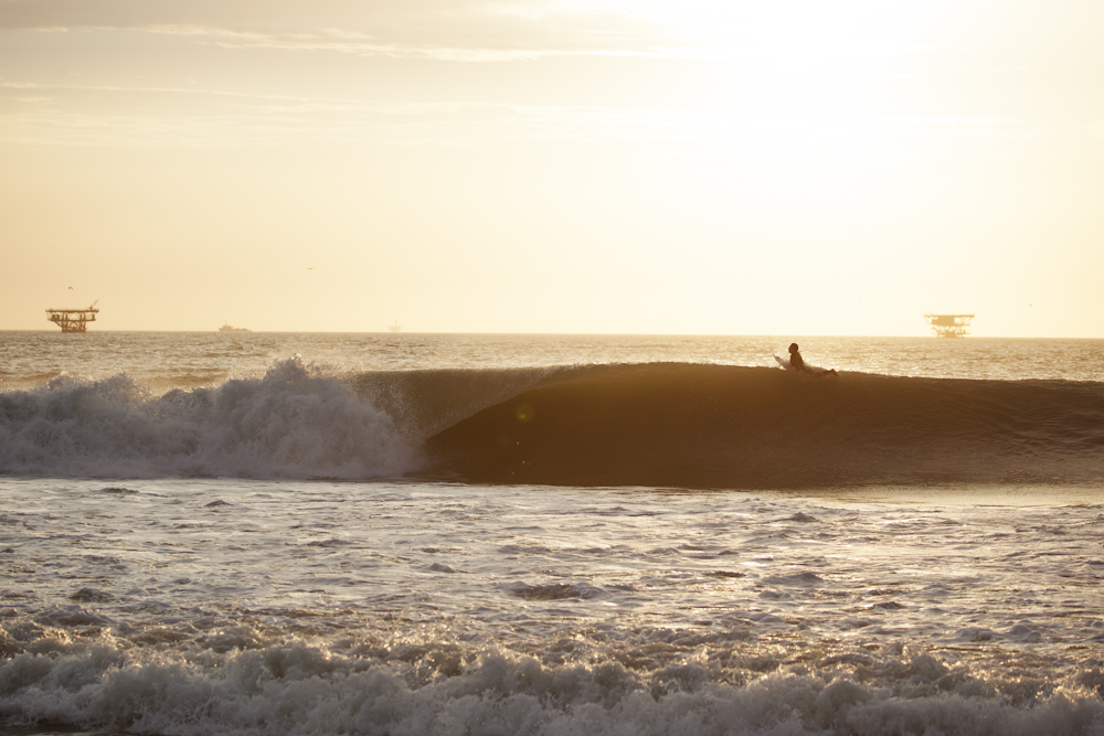 Harold Koechlin paddles over a wave at Lobitos, oil platforms visible on the horizon. Photo: Gary Parker.