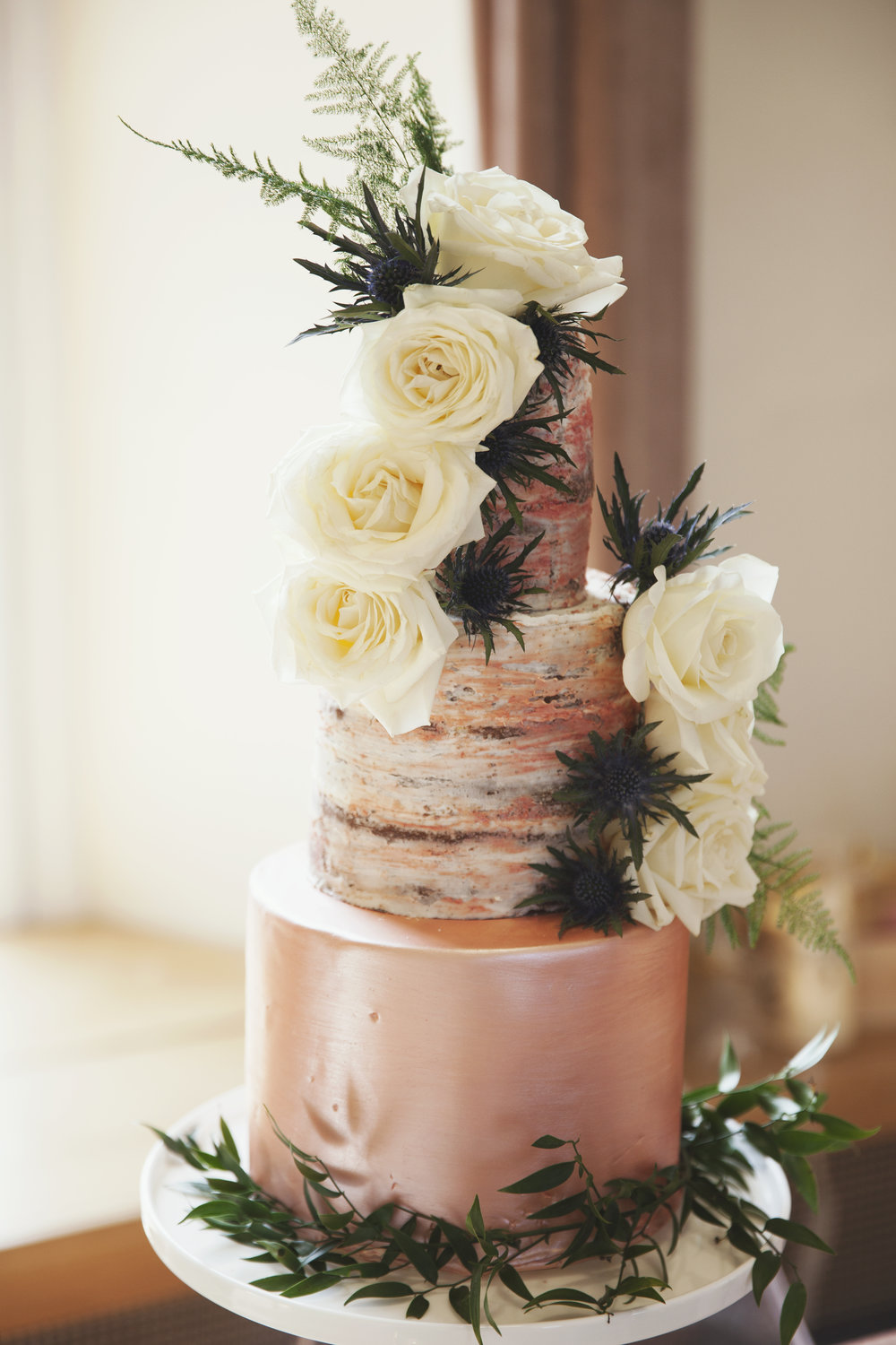 Rose gold watercoloured buttercream on an iced base, fresh roses and thistles