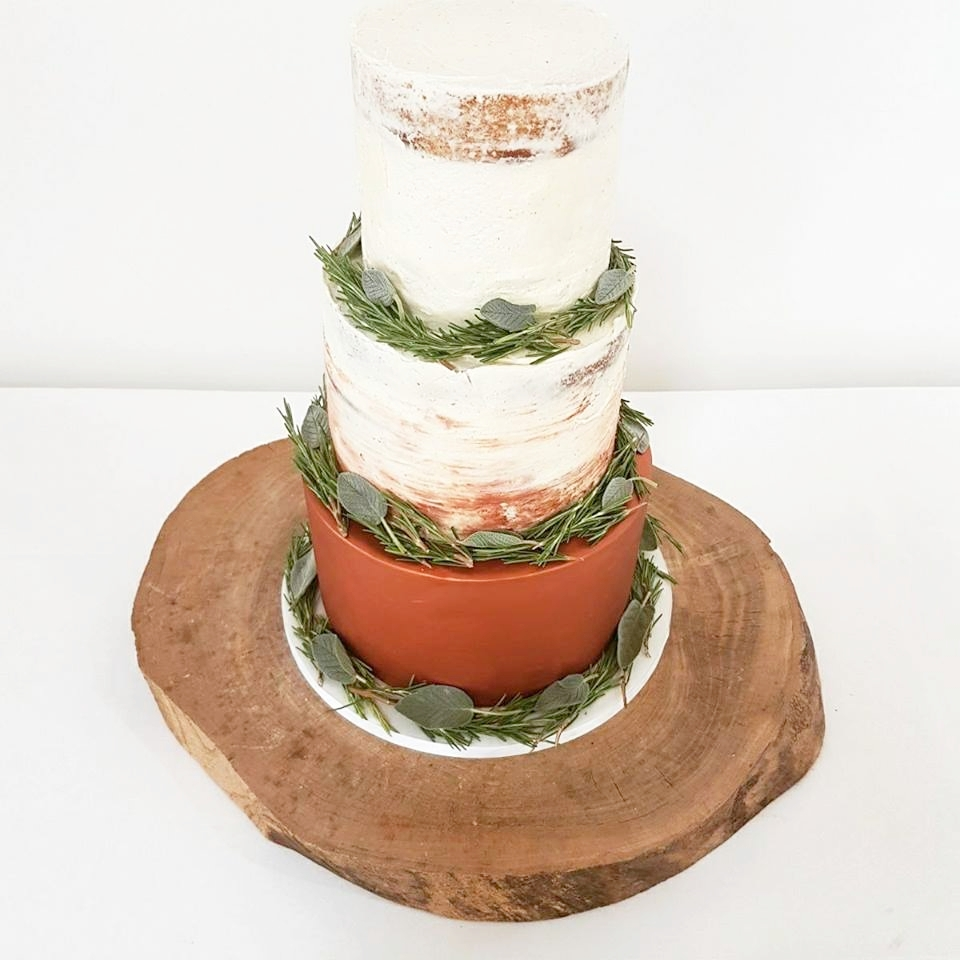A shimmering copper tier with copper watercolour streaks through the buttercream and decorated with fragrant fresh herbs - perfect for a modern rustic wedding at the inimitable  Crear