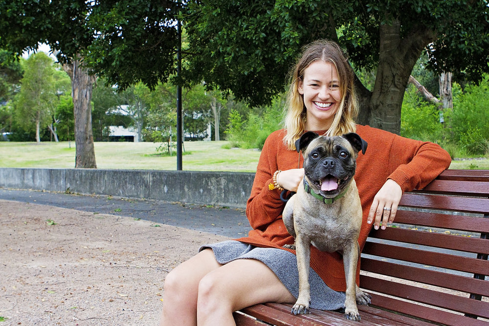 Pug dog sitting on bench with his mum at Sydney Park for professional pet photos