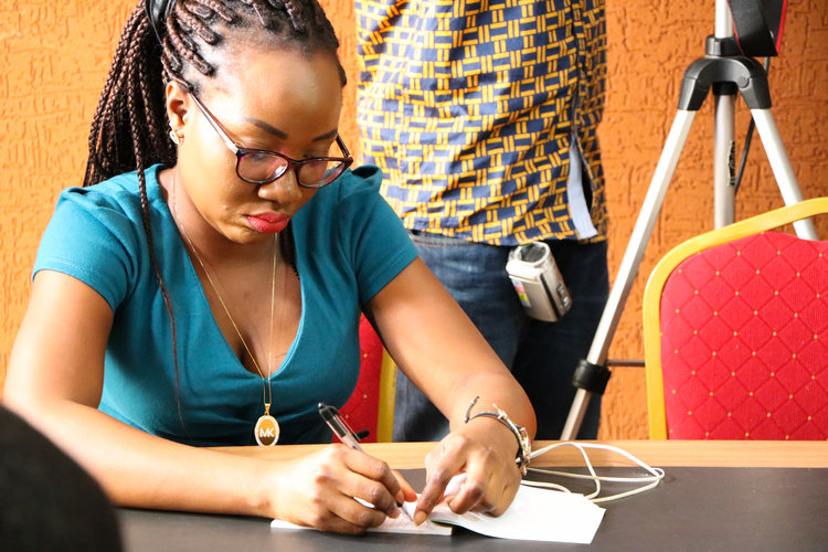 A journalist from GTV takes notes during the conference