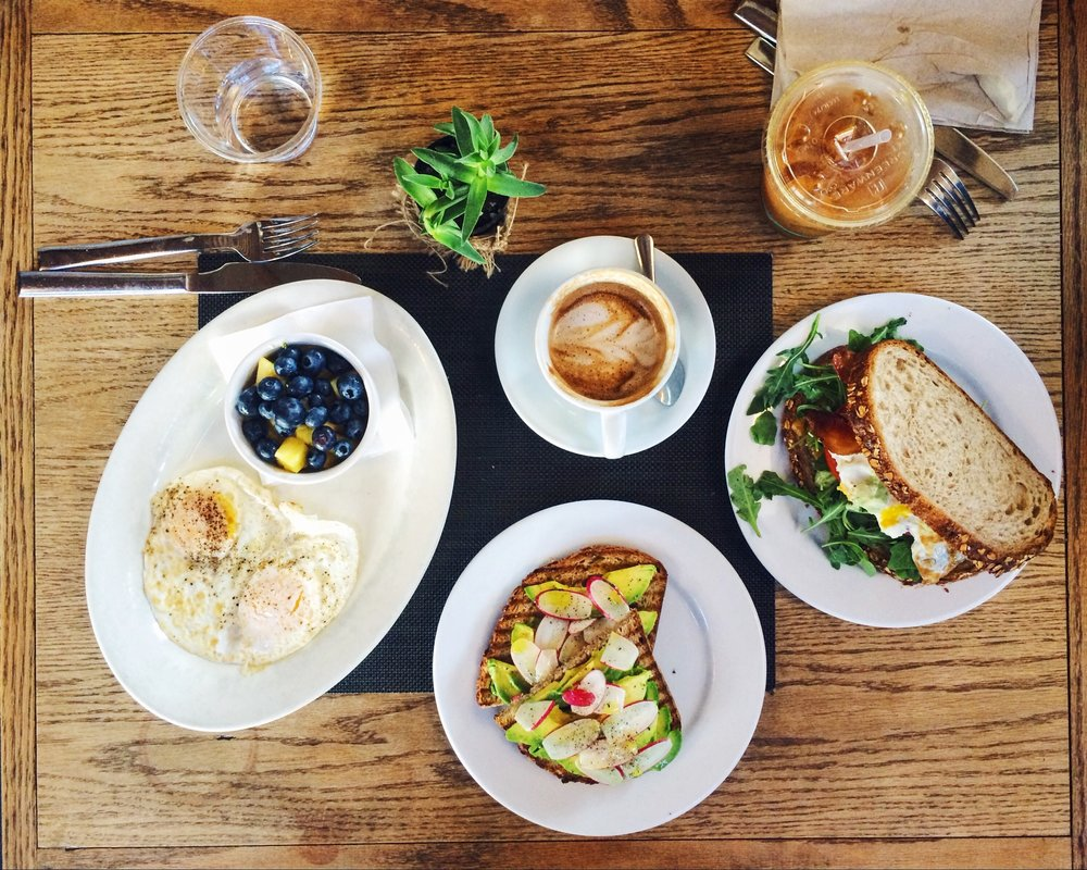 clockwise from left: two eggs, side of fruit, almond milk cappuccino, iced coffee, breakfast sandwich, avocado toast
