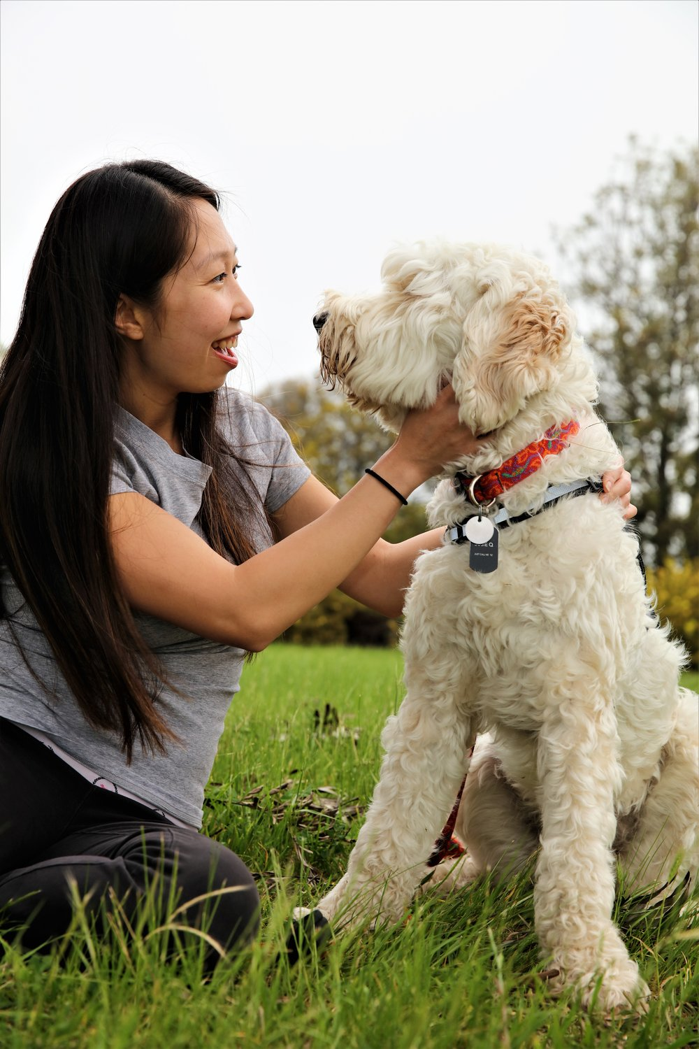 An Asian woman with long black hair smiling at her companion dog while the dog looks back at her.