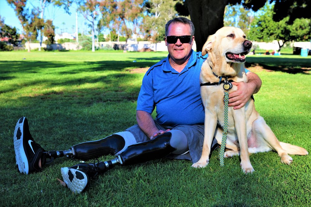 A veteran with prosthetic legs sits with his arm around his golden labrador as they smile for the camera.  Photo by Cheyanne Richert