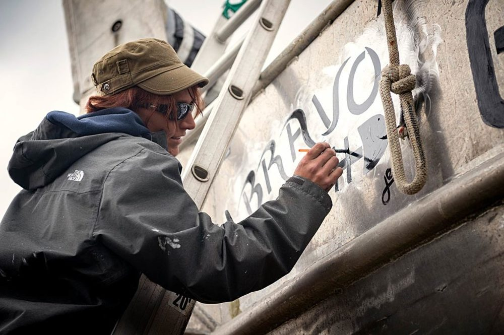 Jennifer Strassel, from Ketchikan, AK, puts the finishing touches on a design and the F/V Bravo's name.