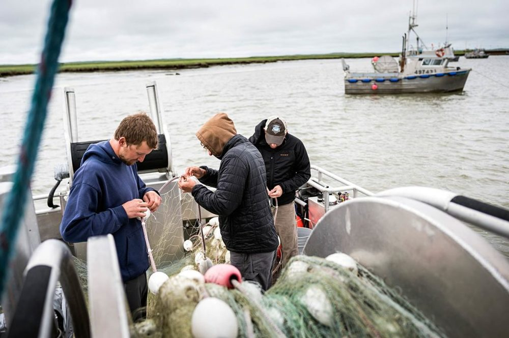 (From left) Burke Bohnsack, Jonathan Adams, and Jason Kohlhase mend the net aboard the F/V Icy Bay, while anchored in Dago Creek during a fishing closure in Ugashik. Fishermen are constantly doing repairs during the season to keep their nets and boats in shape to catch the most fish they can during their short season.
