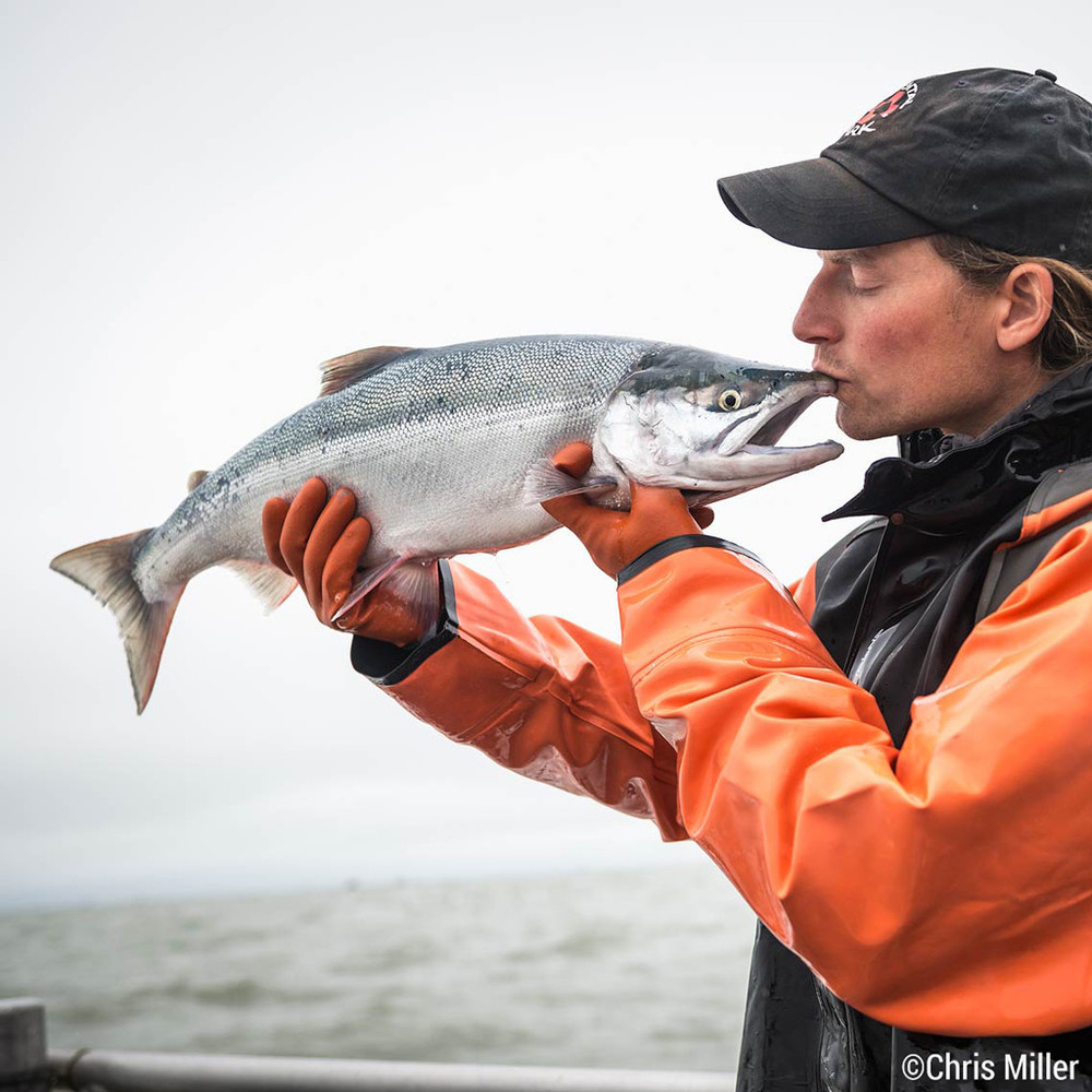 Jonathan Adams kisses the F/V Icy Bay's first sockeye during the first opener of the season in Egegik, Alaska. Millions more of these beauties are on the way.