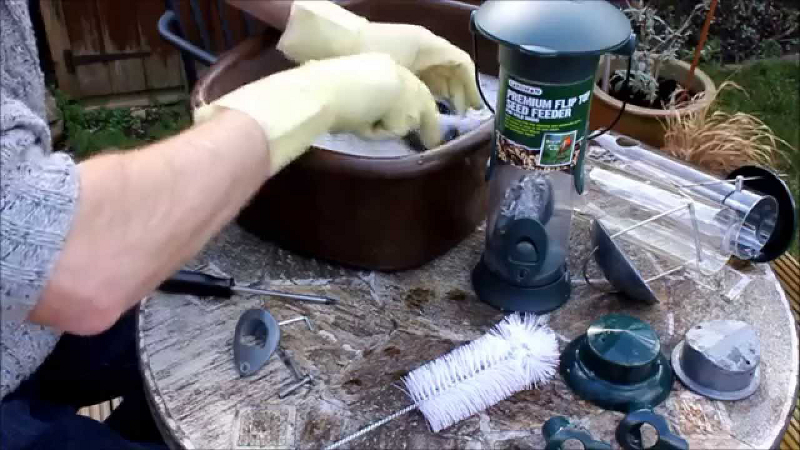 Disassemble your feeder if possible and soak it warm soapy water. Use brushes to clean caked on debris.