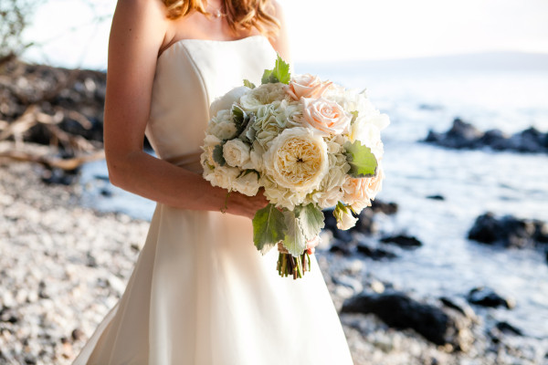 Bride holds wedding bouquet at Maui beach
