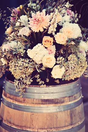 close up of floral arrangement on wine barel