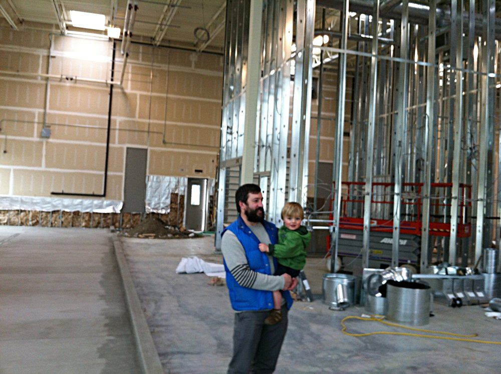 Josh Pfriem and his child in 2012 before the brewery was complete. Here Josh Pfriem is explaining where the mash tun and fermenters will go.