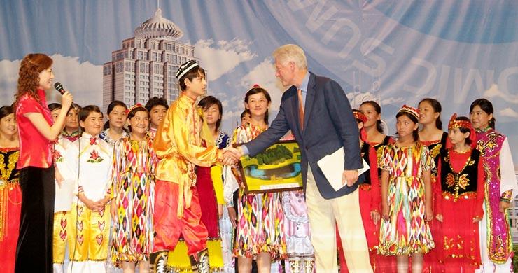 Bill Clinton receiving gift from the children of Xinjiang