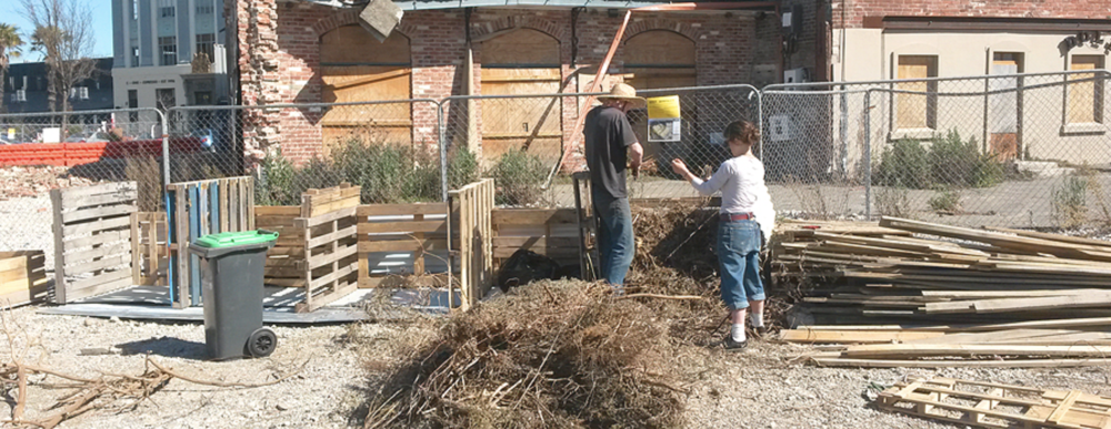 Bailey and Liv Worsnop building  the first  compost heap at Agropolis at its original location on High Street. Over the back fence is now Smash Palace and the site has reverted to being a carpark again!