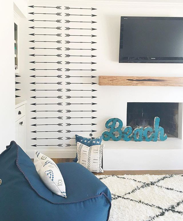 All the elements of our light and airy playroom are coming together. These arrow decals from @urbanwalls were the perfect alternative to wallpaper since that budget went to redoing the fireplace. 😜 #almostdone