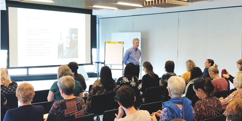 Image: Man standing in front of an audience to the right of a projector screen. Audience have their back to the camera.