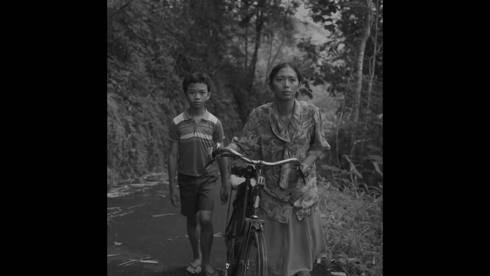 Eden Junjung / Indonesia / 2016 / Javanese / 17min   Dyah and her son travel to the city to make a dead certificate for her husband, Wiji Thukul, who is an Indonesian poet. Dyah's journey turned into something strange since her family holds into belief that he is still alive.   Director:  Eden Junjung studied in Film and Television department in Indonesia Institute of the Arts in Yogyakarta. He started his debut in the film as assistant editor, including Another Trip to The Moon and Aach Aku Jatuh Cinta. Bunga Dan Tembok (Flowers in the Wall) is the first fiction short film that he wrote and directed selected in Jogja NETPAC Asian Film Festival 2016 for Lights of Asia category and international fiction competition in Bogota Short Film Festival 2016 in Coloumbia.   Producer:  Siska Raharja
