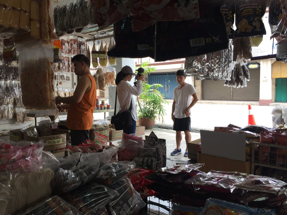 """""""In the shop that was selling salted fish (Kuantan is famous for its salted fish), I was filming Jacky saying his monologue as the ending of my film. We also borrowed power sockets from the boss to charge the camera batteries so I took as long as possible to film Jacky."""" - Elise Shick"""