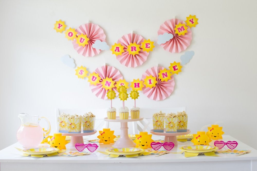 Must-Haves for celebrating summer in style with a 'You are my Sunshine' themed party - Hang pink paper fans with 'You are my sunshine' banner on wall behind dessert table. From Andressa of Twinkle Twinkle Little Party - as seen on www.FestiveFetti.com