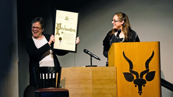 """Catherine Werner (at right), the sustainability director for the City of St. Louis, reads a proclamation held by Whitney R. Harris World Ecology Center interim Director Patricia Parker. The proclamation from Mayor Lyda Krewson declared April 20, 2018, """"Edward O. Wilson Day in the City of St. Louis""""."""