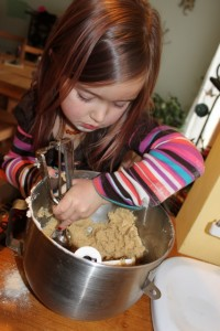 child scooping cookie dough