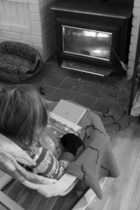 child warming themselves in front of fireplace