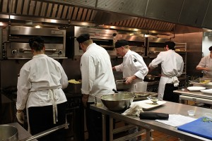 culinary students finishing dishes at the stove