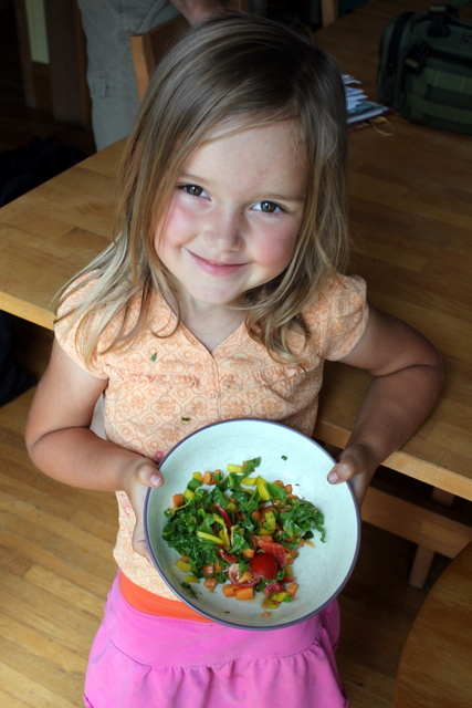 child holding a salad she created