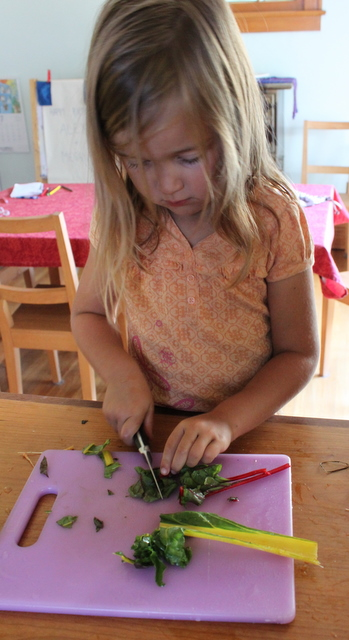 child cutting swiss chard for salad