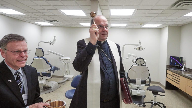 Bishop Robert J. Cunningham blesses the renovated and expanded facilities at Amaus Dental Services in Syracuse Feb. 10. He is assisted by Dr. Robert Fangio, an Amaus volunteer dentist who is also a deacon at Holy Family Church in Syracuse. (Sun photo | Chuck Wainwright)