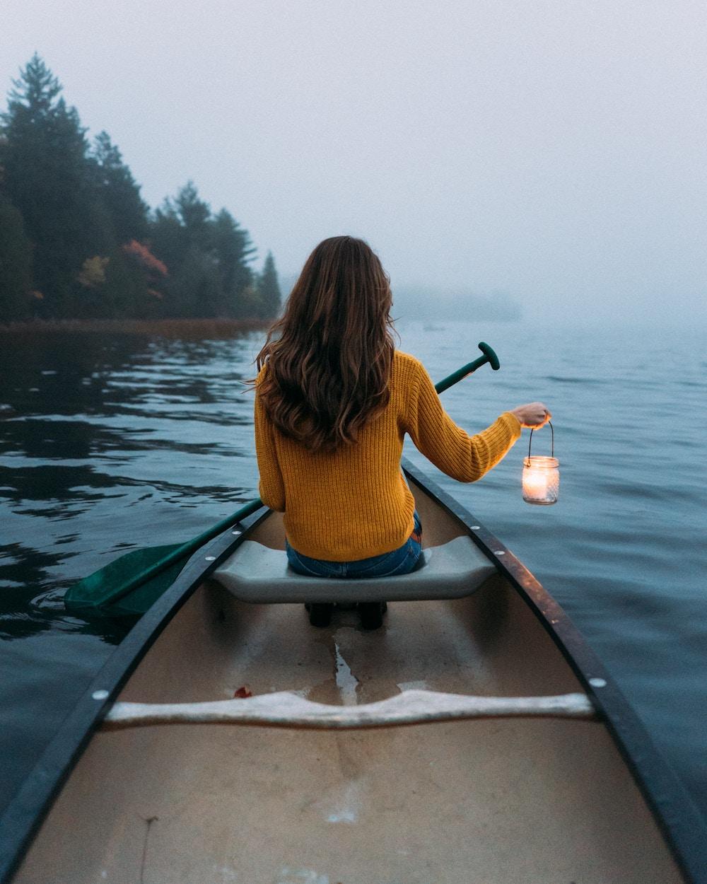 Femme assise sur un bateau, naviguant sur l'eau, lanterne à la main.
