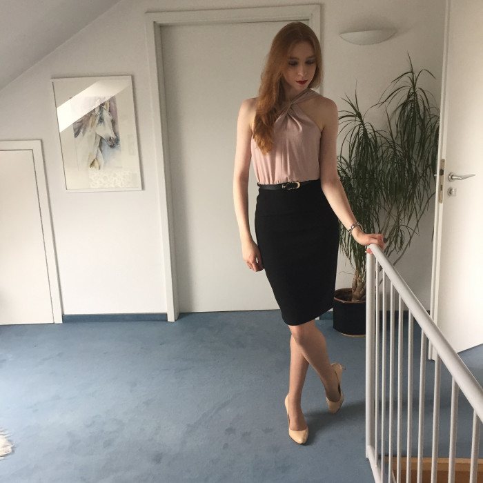 Caroline wears a black and pale pink dress from Miss Selfridge, a black belt emphasising the waist.